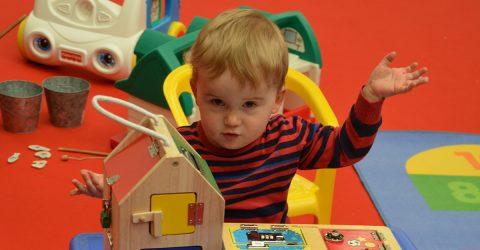 Un petit garçon âgé de 1 an joue avec des jouets en bois pour travailler la motricité et l'éveil.
