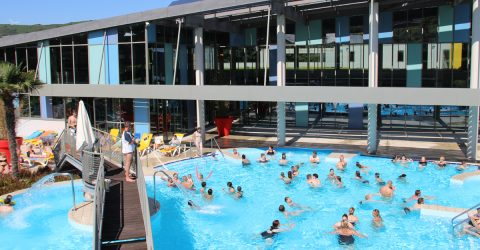 Une trentaine de personnes s'amusent dans la piscine extérieure. Un petit groupe à gauche se repose sur les transats au soleil. Ils sont surveillés par les maîtres nageurs postés sur la passerelle en bois.