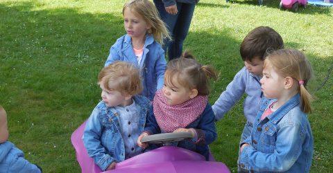 La scène se passe en extérieur sur un coin de pelouse. Deux enfants de 2 ou 3 ans sont dans une voiture en plastique. Ils sont entourés de 3 autres enfants du même âge.