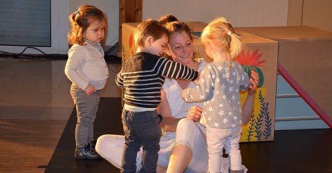 Une animatrice de la structure petite enfance est assise au sol. Elle est entourée par 3 enfants âgés de 2 ou 3 ans. Le petit garçon regarde et touche quelque chose sur le pull d'une petite fille blonde. La deuxième fillette brune observe la scène.