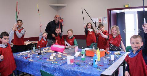 Neuf enfants et l'animateur du centre de loisirs sont en activité peinture autour d'une table. Ils brandissent des bâtons en bois coloré