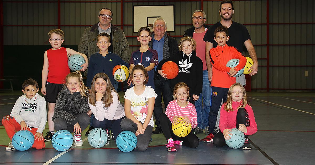 Une dizaine d'enfants prennent la pose avec deux élus, un animateur et le responsable Ludisport76. Ils tiennent dans leurs mains des ballons de basket.