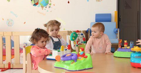 """La scène se passe à la micro-crèche """"La Petite Pomme"""". Trois enfants jouent autour d'une table en bois avec des jeux d'éveil."""