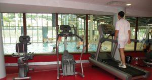 Un homme pratique le tapis électrique dans la salle de cardio. Il a vu sur l'ensemble de l'espace aquatique.