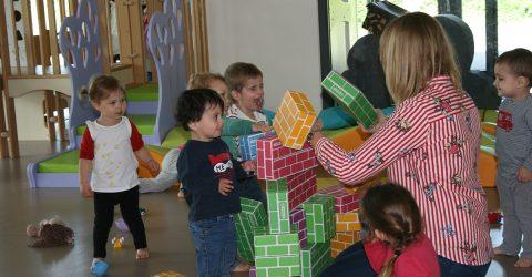 Enfant jouant encadrés par une profesionnelle de la petite enfance