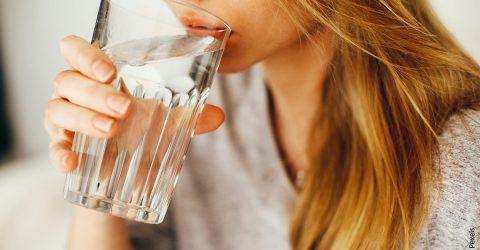 visage d'une femme buvant un verre d'eau